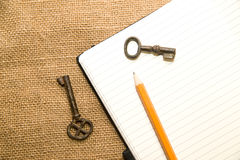 Opened notebook, keys and pencil on the old tissue Stock Photos
