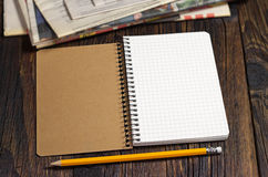 Opened notebook and newspaper Stock Images