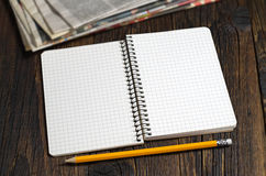 Opened notebook and newspaper Stock Image