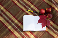 Opened notebook, pen and apple on plaid with autumn leaves. Royalty Free Stock Photos