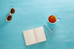 Opened notebook with pen, cup of tea and sunglasses on blue wooden table. Top view. Writing, blogging concept Royalty Free Stock Photography