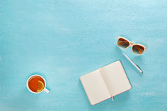 Opened notebook with pen, cup of tea and sunglasses on blue wooden table. Top view. Writing, blogging concept stock image
