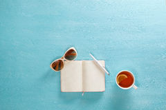 Opened notebook with pen, cup of tea and sunglasses on blue wooden table. Top view. Writing, blogging concept Stock Photo
