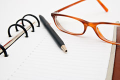 Opened notebook with pen and glasses. Pen and glasses  lying on opened notebook Stock Photography