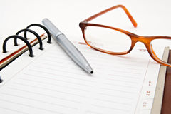 Opened notebook with pen and glasses. Pen and glasses  lying on opened notebook Royalty Free Stock Photos
