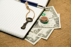 Opened notebook, pen, key and money on the old tissue Royalty Free Stock Photo