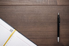 Opened notebook and pen on wooden table Royalty Free Stock Images