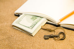 Opened notebook, pencil, key and money on the old tissue Stock Photos