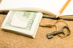Opened notebook, pencil, key and money on the old tissue Royalty Free Stock Image