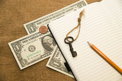 Opened notebook, pencil, key and money on the old tissue Royalty Free Stock Photography