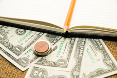 Opened notebook, pencil, key and money on the old tissue Royalty Free Stock Photo