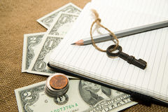 Opened notebook, pencil, key and money on the old tissue Royalty Free Stock Photos