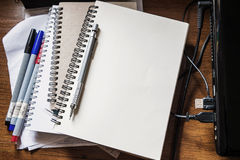Opened notebook with pencil, marker pen and laptop on working table Stock Image