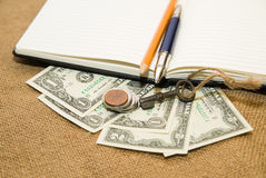 Opened notebook, pencil, pen,  key and money on the old tissue Royalty Free Stock Images