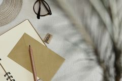 The opened notebook, pencil, sharpener, envelope, spectacles, hat on the table and shadow royalty free stock photos