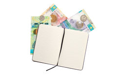 Opened notebook and some money of kazakhstan over Royalty Free Stock Photo