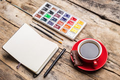 Opened notebook with watercolour paints Royalty Free Stock Photos