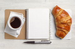Opened notepad, croissant and coffee Royalty Free Stock Photos