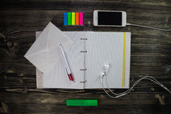 Opened notepad with envelope and headphone with phone. Stock Photo