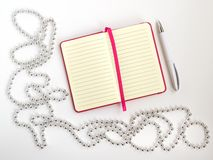 Opened notepad with lined paper, white ballpoint pen and silver colored bead christmas garland on a light background, festive flat stock photo