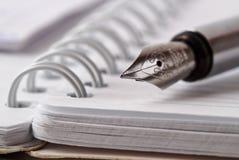 Opened notepad with metallic fountain pen Stock Photos