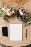 Opened notepad with pen and black smart phone on wood table in coffee shop in morning scene. Top view royalty free stock photos