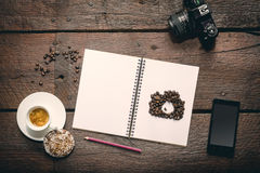 Opened notepad on the table. Blank opened notepad on the table, Cup of espresso, honey-cake, coffee beans, smatphone and camera Royalty Free Stock Images