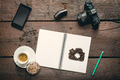 Opened notepad on the table. Blank opened notepad on the table, Cup of espresso, honey-cake, coffee beans, smatphone and camera Stock Photos