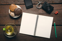 Opened notepad on the table. Blank opened notepad on the table, Cup of tea, honey-cakes, smatphone and camera Royalty Free Stock Photo