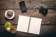 Opened notepad on the table. Blank opened notepad on the table, Cup of tea, honey-cakes, smatphone and camera Royalty Free Stock Images