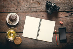 Opened notepad on the table. Blank opened notepad on the table, Cup of tea, honey-cakes, smatphone and camera Royalty Free Stock Image