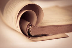 Opened old book in sepia and vintage color tone , selective focus Stock Photos
