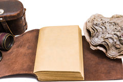 Opened old leather book isolated on white background. With travel accesories Royalty Free Stock Images