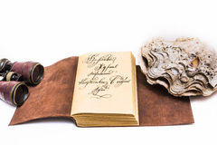 Opened old leather book. With sea shell and binoculars Royalty Free Stock Photography