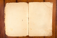 Opened old softcover book on a wooden background Stock Photos
