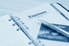 Opened organizer, pen and credit card. Expenses section. Blue toned Stock Image