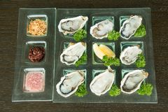 Oysters on glass plate with spicy sauce. Opened Oysters on glass plate with spicy sauce Stock Photography