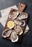 Opened oysters and lemon over ice Royalty Free Stock Photography