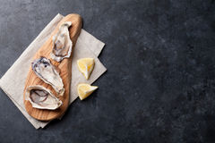 Opened oysters and lemon Stock Photo