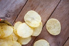 Opened pack with potato chips over table Royalty Free Stock Image