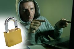 Opened padlock composite with young dangerous and skilled hacker manprogramming on laptop computer system cracking password in stock images