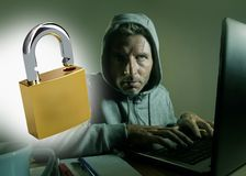 Opened padlock composite with young dangerous and skilled hacker manprogramming on laptop computer system cracking password in royalty free stock photography