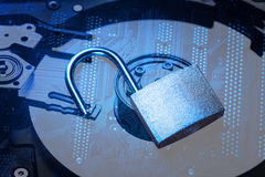 Opened padlock on computer motherboard and hard disk drive. Internet data privacy information security concept. Blue toned image.  stock photography