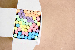 Opened paper box with colorful pieces of chalk for copy space on wooden background. Opened paper box with colorful pieces of chalk for copy space stock photo