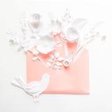 Opened pink envelope full of varios white paper flowers on white background Stock Image