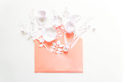 Opened pink envelope full of varios white paper flowers on white background Royalty Free Stock Images