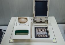 Opened polymerase chain reaction PCR cycler machine with DNA samples.  stock photos