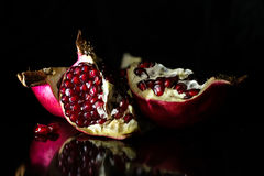Opened pomegranate in black background Stock Photos