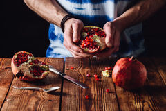 Opened Pomegranate in the Hands. Other Half and Some Seeds on Table Royalty Free Stock Photos