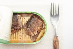 Opened può del pesce con una forcella Immagine Stock